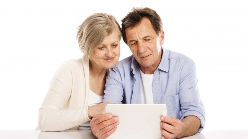 Senior couple using tablet, isolated on white background